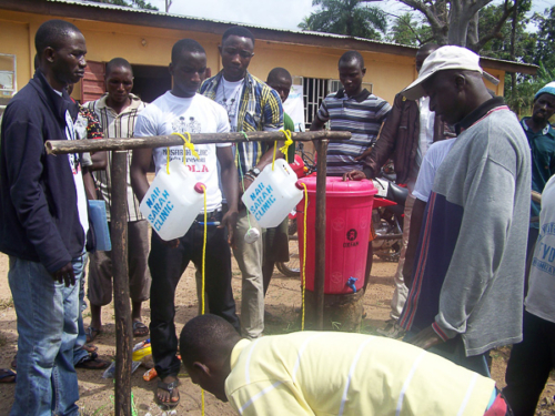 Tippy tap installation at a check point near an OXFAM donated water bucket.